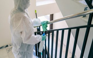 Cleaning handrail wearing PPE